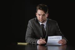Ernster Geschäftsmann, der auf den Vertrag lokalisiert auf Schwarzem zeigt Stockfoto