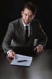 Ernster Geschäftsmann, der auf den Vertrag lokalisiert auf Schwarzem zeigt Lizenzfreie Stockfotos