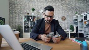 Ernster Geschäftsmann, der die Gelddollar sitzen am Schreibtisch im Büro allein zählt stock video footage