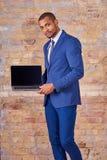 Ernster Geschäftsmann, der Laptopschirm zeigt Stockfoto