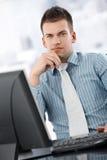 Ernster Geschäftsmann, der am Schreibtisch denkt Stockfotografie