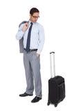 Ernster Geschäftsmann, der sein Gepäck betrachtet Stockfotografie