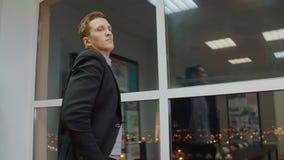 Ernster Geschäftsmann, der ungefähr, denkt vom geschäftlichen Problem zu lösen, wenn Büro geglättet wird stock footage