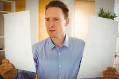 Ernster Geschäftsmann, der zwei Papierblätter hält Stockfotografie