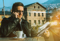 Ernster Geschäftsmann mit Zeitung und Kaffee sprechend durch Mobile Lizenzfreies Stockfoto