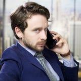 Ernster Geschäftsmann am Telefon im Büro stockbild