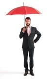 Ernster Geschäftsmann unter rotem Regenschirm Lizenzfreies Stockfoto