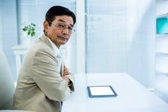 Ernster Geschäftsmann unter Verwendung der Tablette Stockfotos
