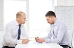 Ernster Geschäftsmann zwei mit Papieren im Büro lizenzfreie stockfotografie
