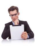Ernster Geschäftsmannmesswert auf seiner Tabletteauflage Stockbild