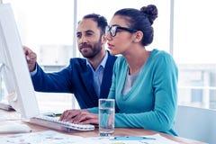 Ernster Geschäftsmann und Geschäftsfrau, die über Computer sich bespricht Lizenzfreie Stockbilder
