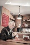 Ernster grauhaariger Mann, der allein in der Cafeteria sitzt stockbild