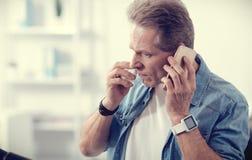 Ernster gutaussehender Mann, der am Telefon spricht Lizenzfreies Stockbild