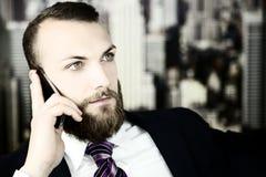 Ernster hübscher Geschäftsmann am Telefon lizenzfreies stockbild