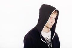 Ernster hübscher junger Mann in den schwarzen Kapuzenpullis schaut weg Stockfoto