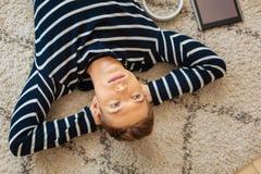 Ernster Jugendlicher, der auf dem Boden und dem Denken liegt Lizenzfreie Stockfotografie