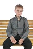 Ernster Junge, der auf einer Bank sitzt Lizenzfreie Stockbilder