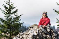 Ernster Junge, der auf einer Klippe steht Lizenzfreie Stockfotografie