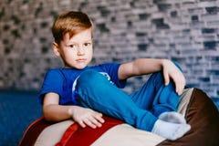 Ernster Junge, der in der Stuhltasche sitzt lizenzfreies stockfoto