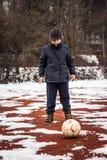 Ernster Junge, der vor Ball steht Lizenzfreies Stockfoto