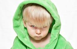 Ernster Junge im grünen Hausmantel stockbilder