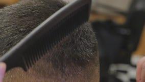 Ernster junger bärtiger Mann, der Haarschnitt durch Friseur erhält Friseursalon-Thema Langsame Bewegung stock video
