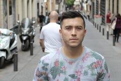Ernster junger eurasischer Mann draußen stockbild