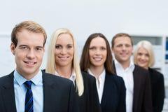 Ernster junger Geschäftsführer mit seinem Team Stockbild