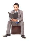 Ernster junger Geschäftsmann, der ein Buch liest Lizenzfreie Stockfotos