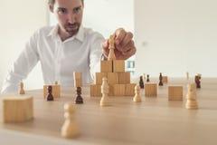 Ernster junger Geschäftsmann, der Königschachfigur auf in Position bringt lizenzfreies stockbild
