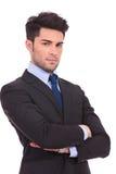 Ernster junger Geschäftsmann, der mit den Händen gekreuzt steht Stockfotografie