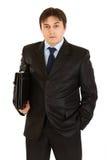 Ernster junger Geschäftsmann mit Aktenkoffer in der Hand Lizenzfreie Stockfotos