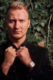 Ernster junger Geschäftsmann tragendes T-Shirt und schwarze Hose mit blauen Augen Stockbilder