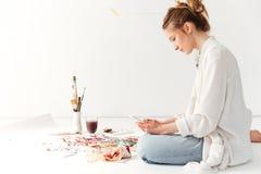 Ernster junger kaukasischer Damenmaler am Arbeitsplatz unter Verwendung des Telefons Lizenzfreie Stockfotografie