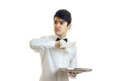 Ernster junger Kellner in einem Hemd, das ein Tuch in der anderen Hand hält, hält den Behälter und blickt in Richtung Lizenzfreie Stockbilder
