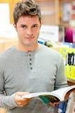 Ernster junger Mann, der ein Buch liest Stockfotografie