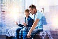 Ernster junger Mann, der nahe seinem Sohn sitzt Stockfotos