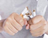 Ernster junger Mann, der Scheren nahe der Zigarette bei der Stellung lokalisiert auf weißem Hintergrund hält stockbild