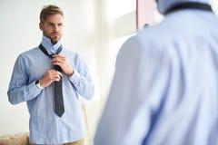 Ernster junger Mann, der vor Arbeit sich kleidet lizenzfreies stockbild