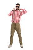 Ernster kühler bärtiger Hippie, der Hosenträger justiert Stockfoto