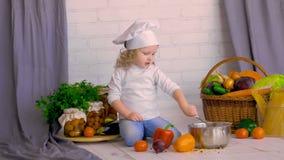 Ernster kleiner Chef mit einem Schöpflöffel kochend in den Küchendekorationen stock video