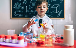 Ernster kleiner Junge, der mit chemischen Flüssigkeiten spielt Lizenzfreie Stockfotos