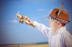Ernster kleiner Junge, der mit einem Spielzeugflugzeug spielt Stockfotografie