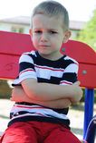 Ernster kleiner Junge, der am Spielplatz sitzt Lizenzfreies Stockfoto