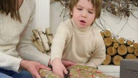 Ernster kleiner Junge, welche seiner Mutter hilft, Packpapier für Weihnachtsgeschenke zu schneiden stock footage