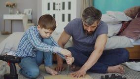 Ernster kleiner Junge wird auf das Einsetzen der Schraube in Stück Hölzer mit Schraubenzieher konzentriert, während sein Vater ih stock video