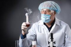 Ernster Kliniker studiert mit Werkzeugen im Labor und Haltenflasche Stockfotografie