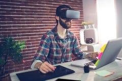 Ernster kreativer Geschäftsmann unter Verwendung der Videogläser 3D und des Laptops Stockfoto