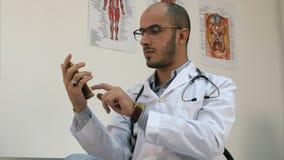 Ernster männlicher Doktor, der auf einem Smartphone simst stockbilder