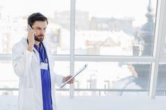 Ernster männlicher Doktor, der am Telefon in Verbindung steht Lizenzfreie Stockbilder